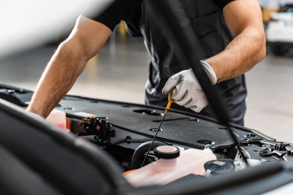Mechanic checking oil level in a car