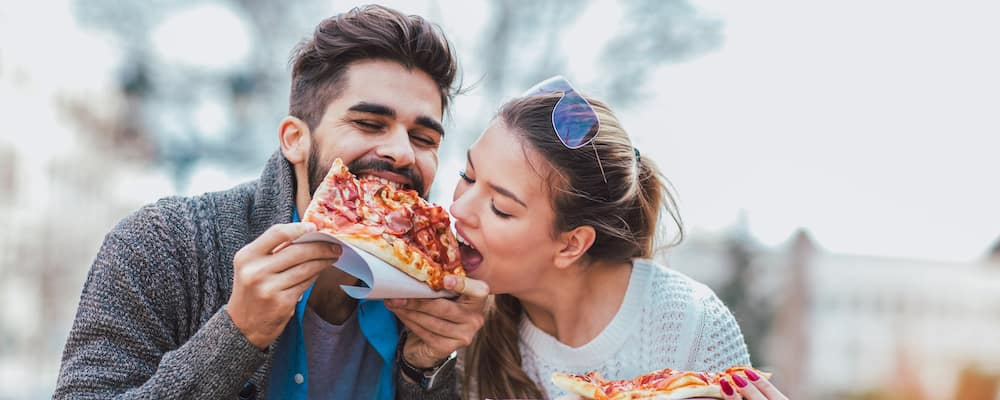 Couple eating pizza outdoors and smiling.They are sharing pizza in an outdoor cafe.