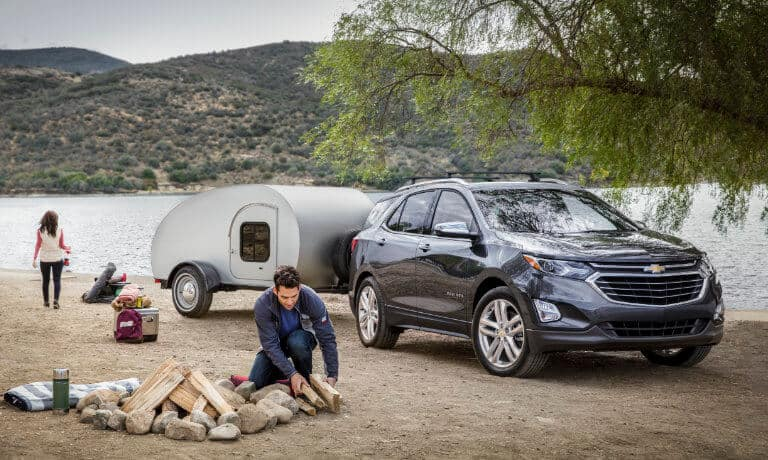 A couple camping next to a lake with their 2020 Chevy Equinox