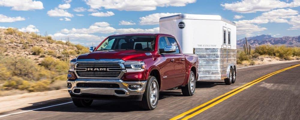 Red 2019 RAM 1500 towing trailer on desert highway