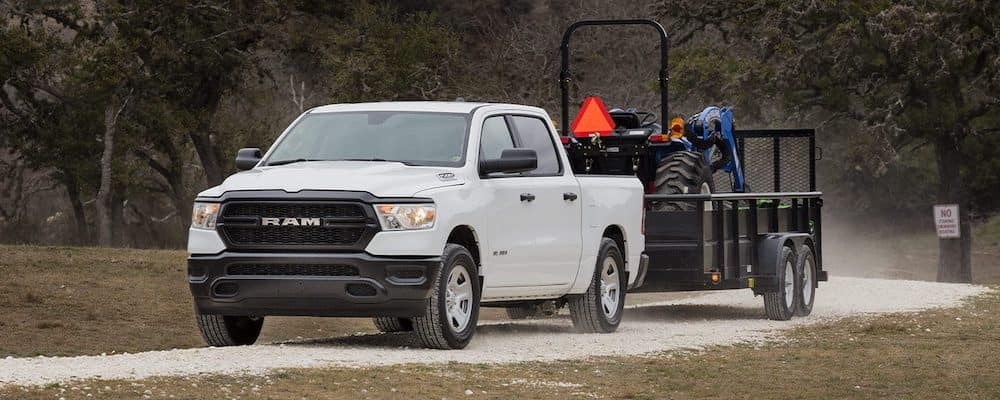White 2019 RAM 1500 towing tractor on truck bed on gravel road