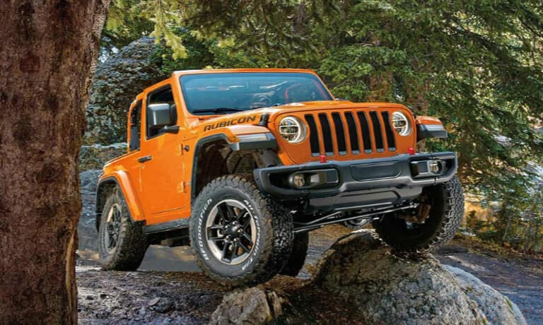 Orange Jeep Wrangler Off-roading in the woods.