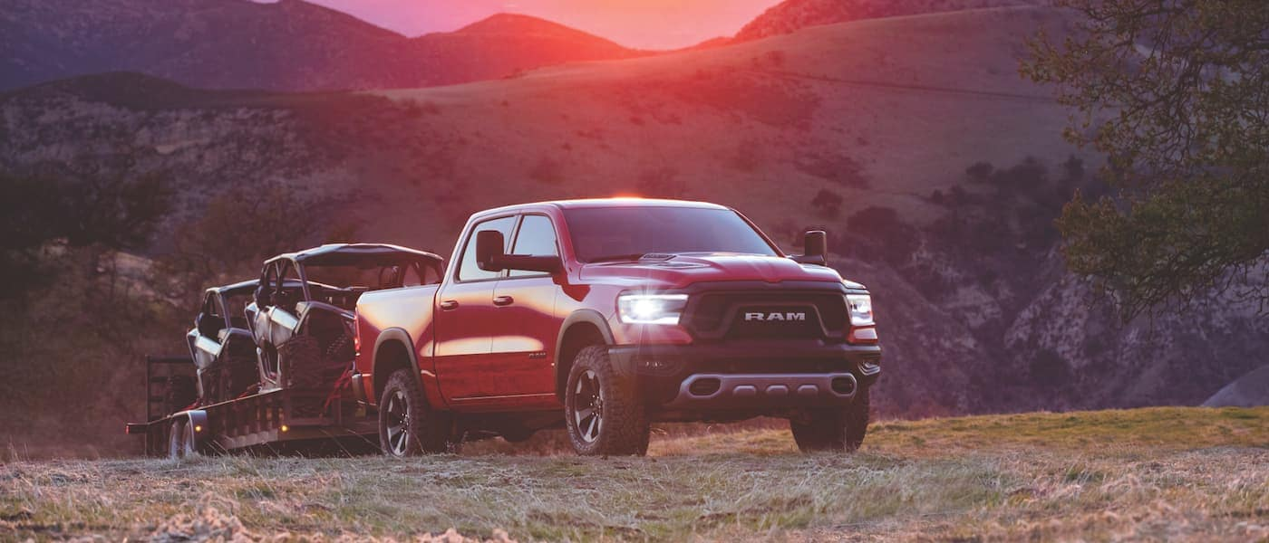 2021 Ram 1500 towing ATVs in a field