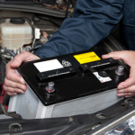 A car mechanic replaces a battery.