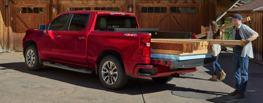 Unloading truckbed of red Chevy Silverado
