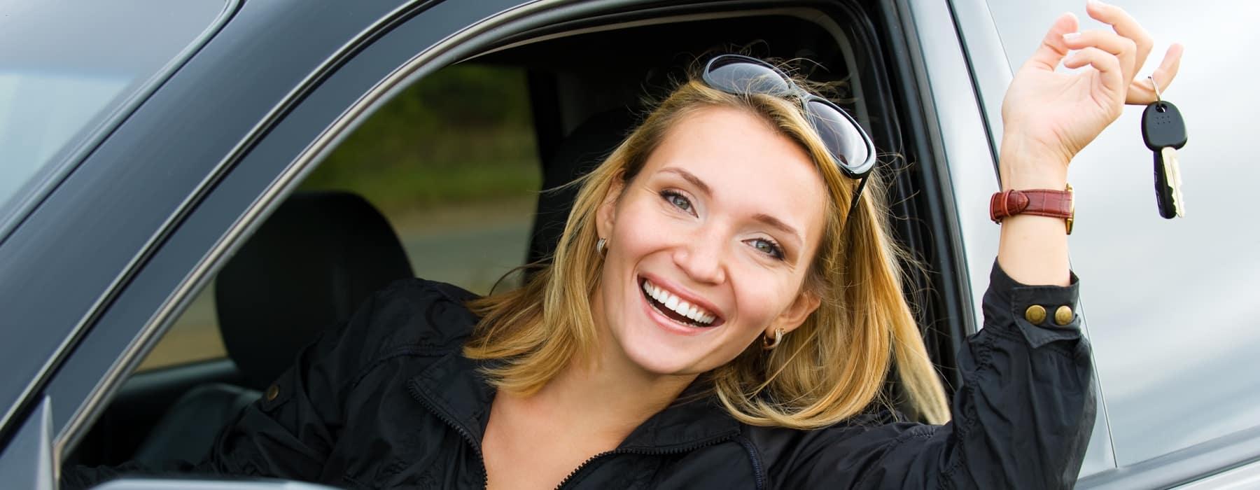 woman in car holding car keys