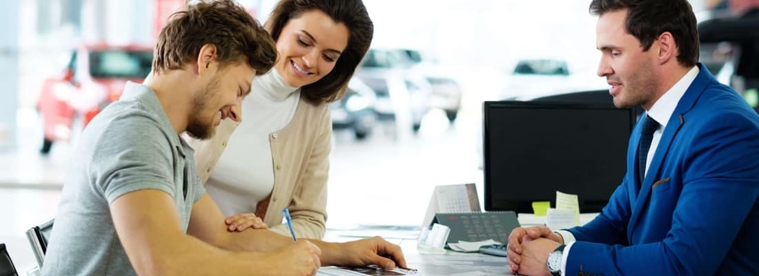 couple signing document at dealership