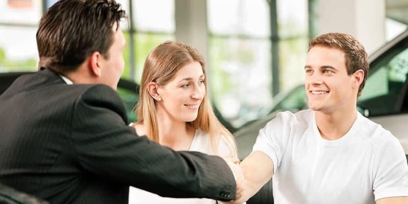 Couple Shaking Hands with a Salesman