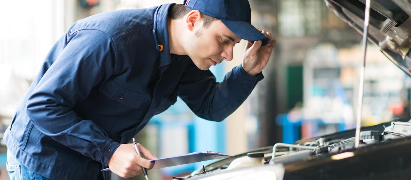 Mechanic over open car hood