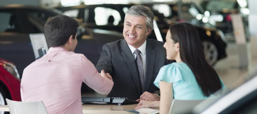 Couple sitting with an automotive finance representative