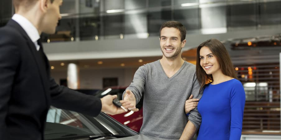 Couple receiving new car keys from a car salesman