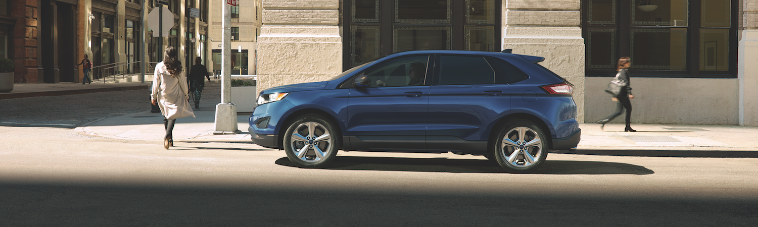 A Blue Ford Edge Stapped In Front Of A Crosswalk