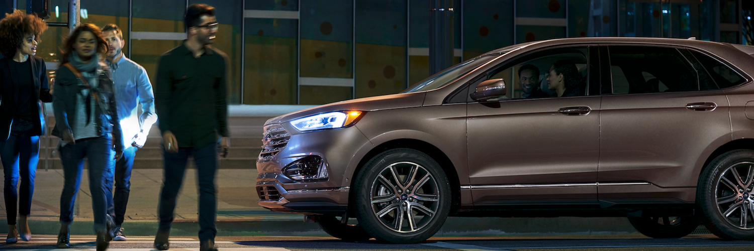 A 2019 Ford Edge parked at a busy crosswalk