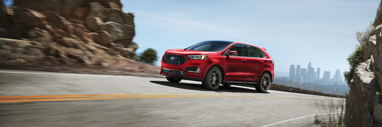 A red 2019 Ford Edge driving away from the city