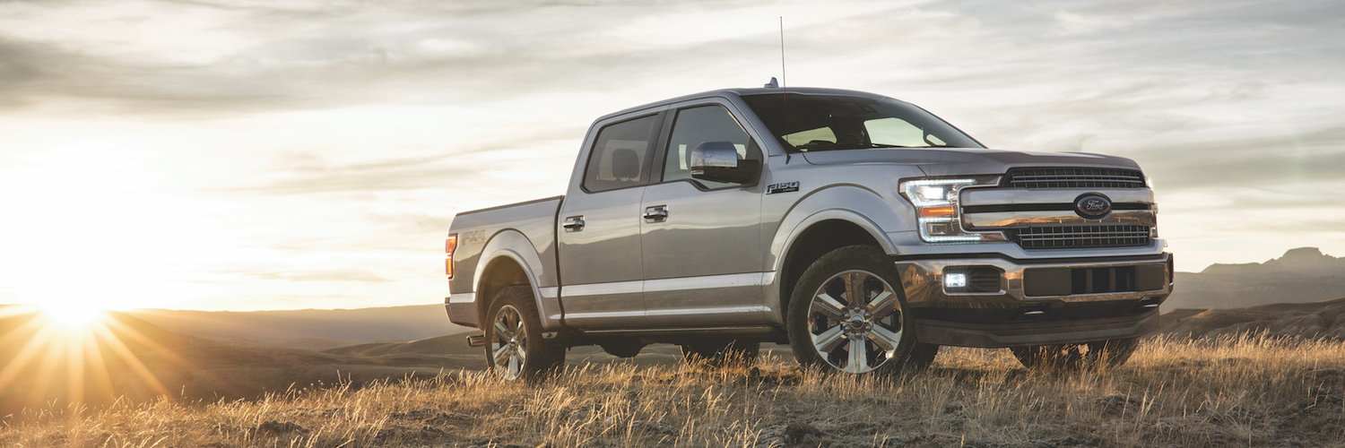 A silver Ford F-150 parked on a hilltop during the sunset