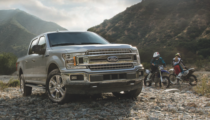 Ford F-150 and two motorcyclists waiting in a mountain valley