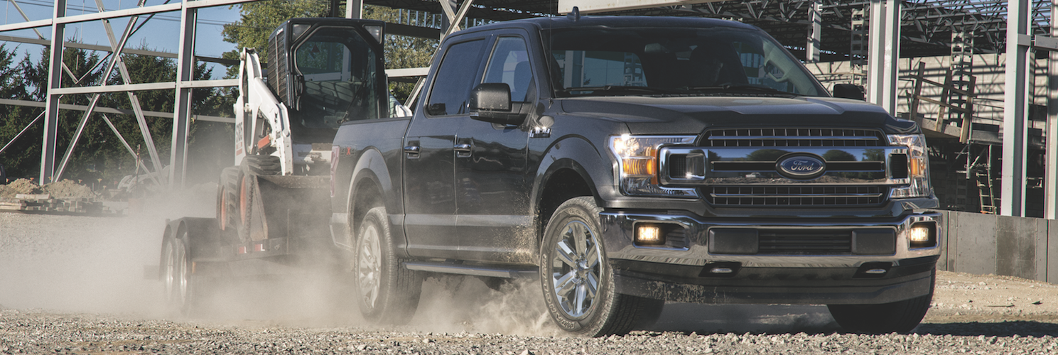 A black Ford F-150 hauling equipment around at a construction site