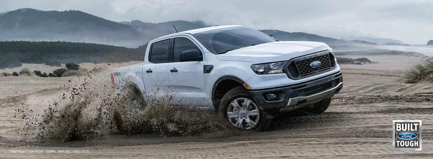 A white 2019 Ford Ranger driving through mud