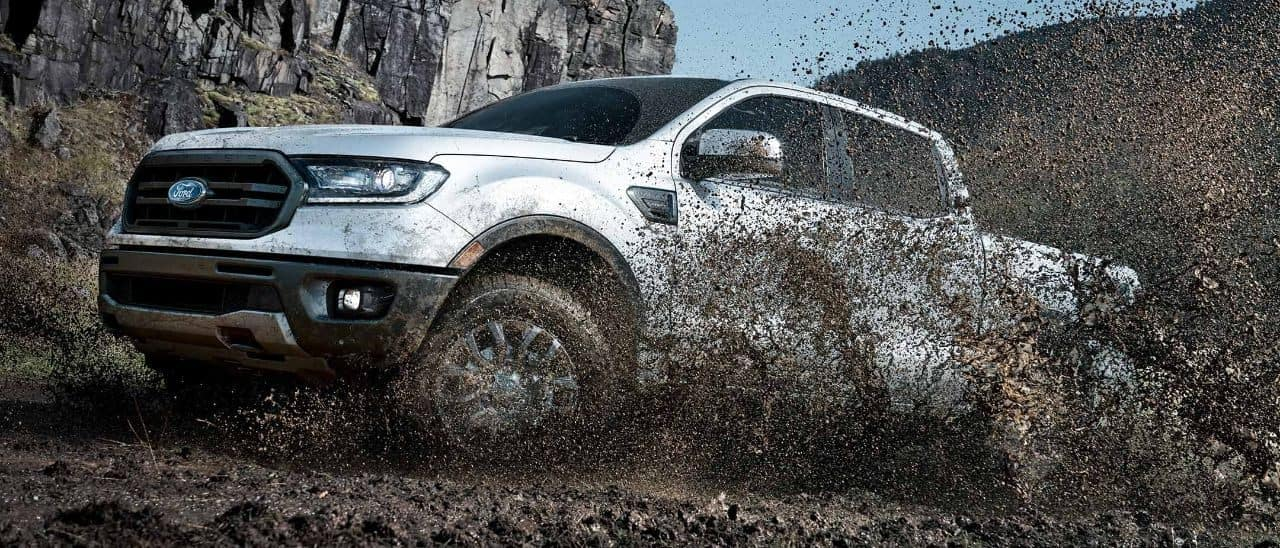 A white 2019 Fordr Ranger driving through the mud