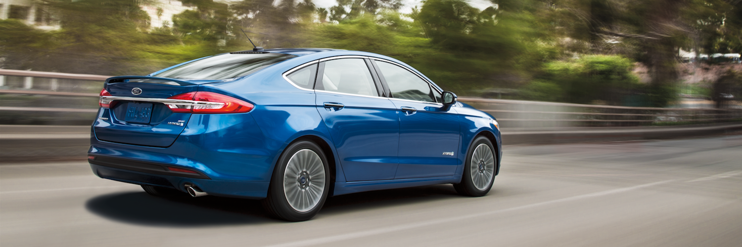 A blue Ford Fusion driving quickly down the road