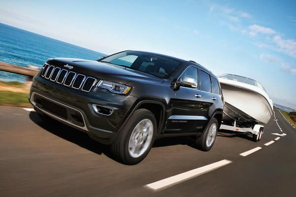 Black Jeep Grand Cherokee towing a boat with a body of water in the background