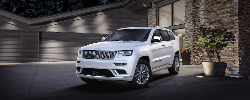 White Jeep Grand Cherokee parked on a driveway at night