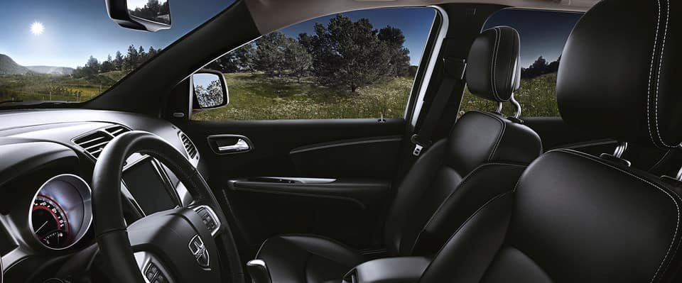 Side view of 2019 Dodge Journey front seats driving past trees