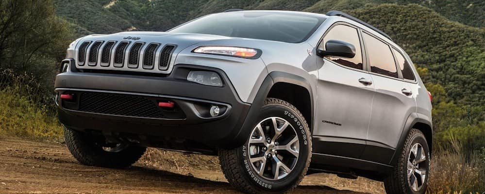 Silver 2018 Jeep Cherokee driving up hill on mountains