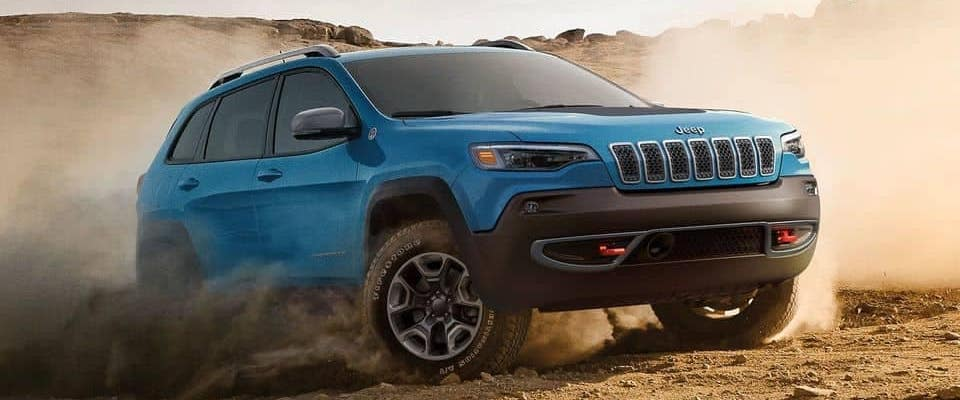 Blue 2019 Jeep Cherokee driving on dusty off-road