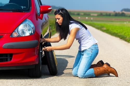 Woman changing tire
