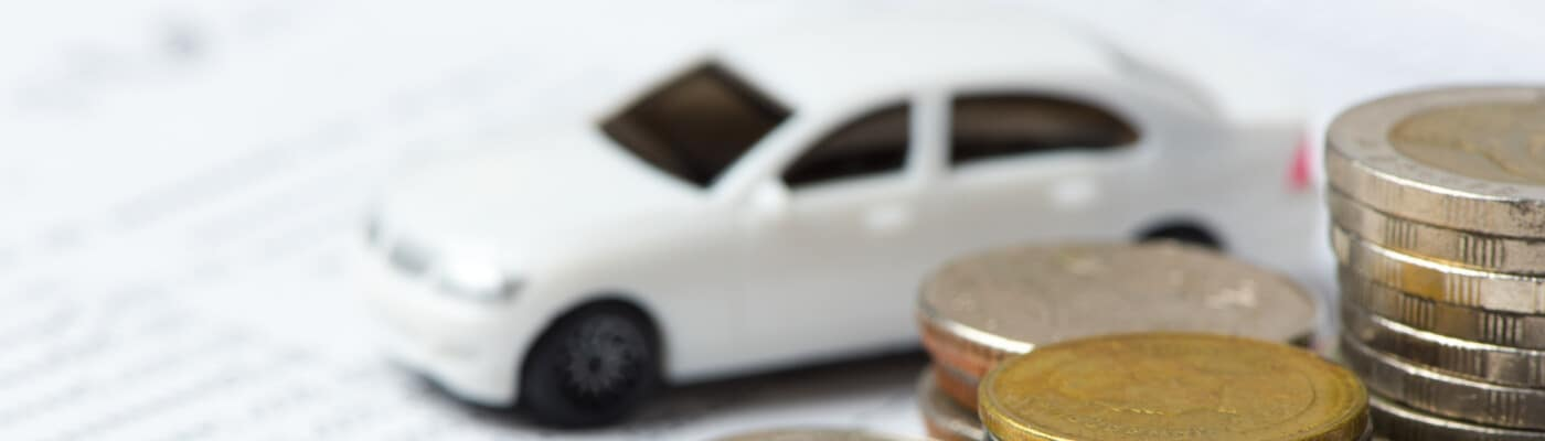 finance paperwork with tiny car and coins