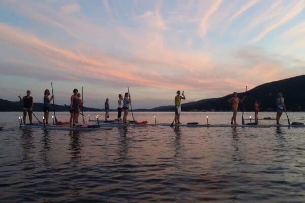 Paddle Boarders Lined Up At Night