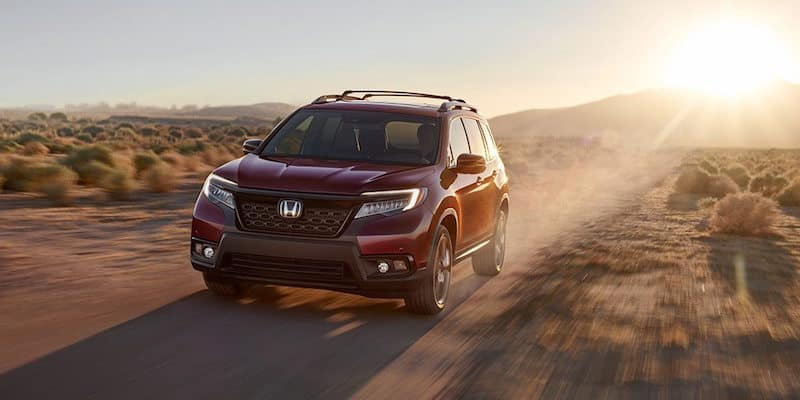 Red Honda Pilot driving at sunset
