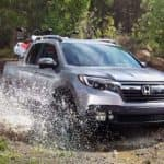 Silver Honda Ridgeline driving through creek