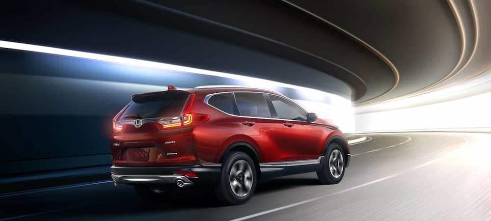 Red CR-V driving under a curved overpass