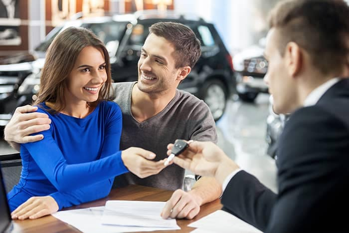 Couple Receiving Car Keys After Signing Papers