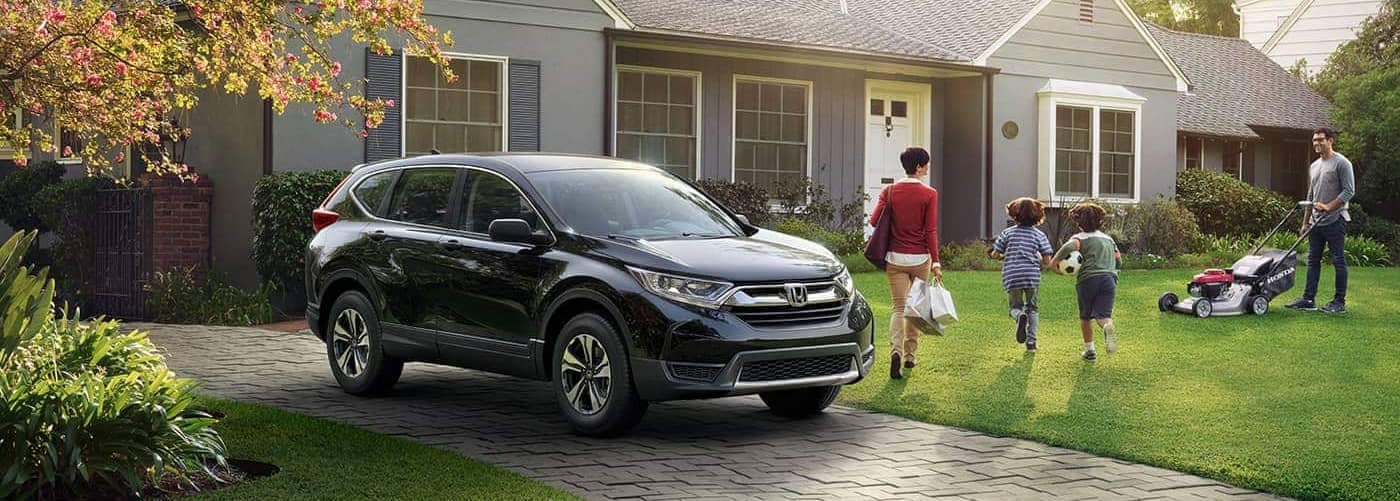 Honda CR-V Parked in Front of House with Family Outside