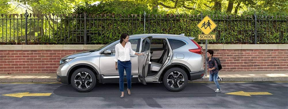 Mom holding door open for child to jump in a 2019 Honda CR-V