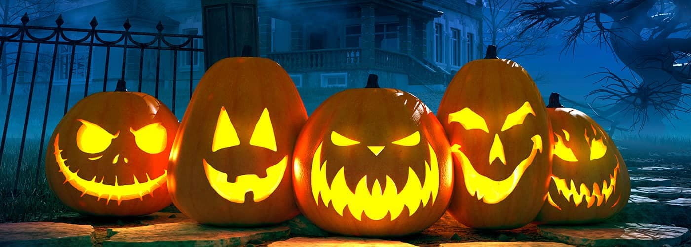 Carved Pumpkins in front of Haunted House