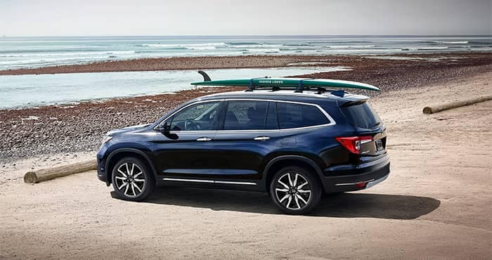 Honda Pilot Parked on Beach with Surfboard on roof rail