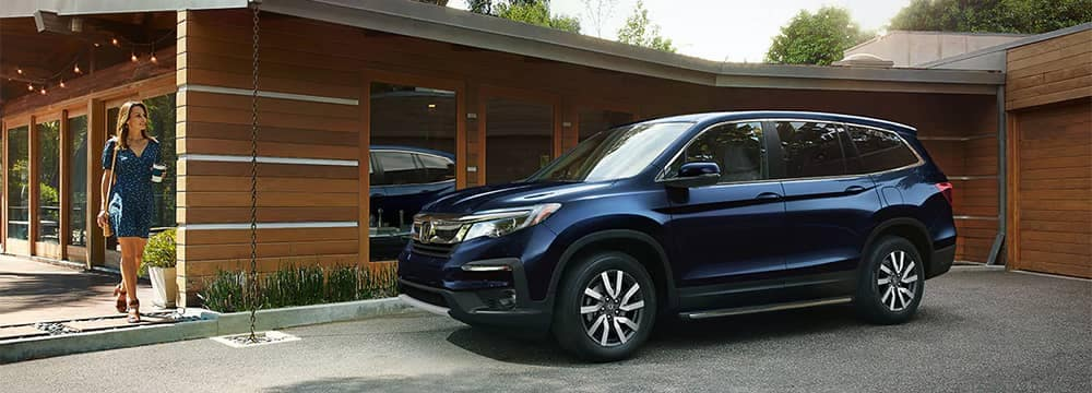 Woman walking out of house to a 2020 Honda Pilot
