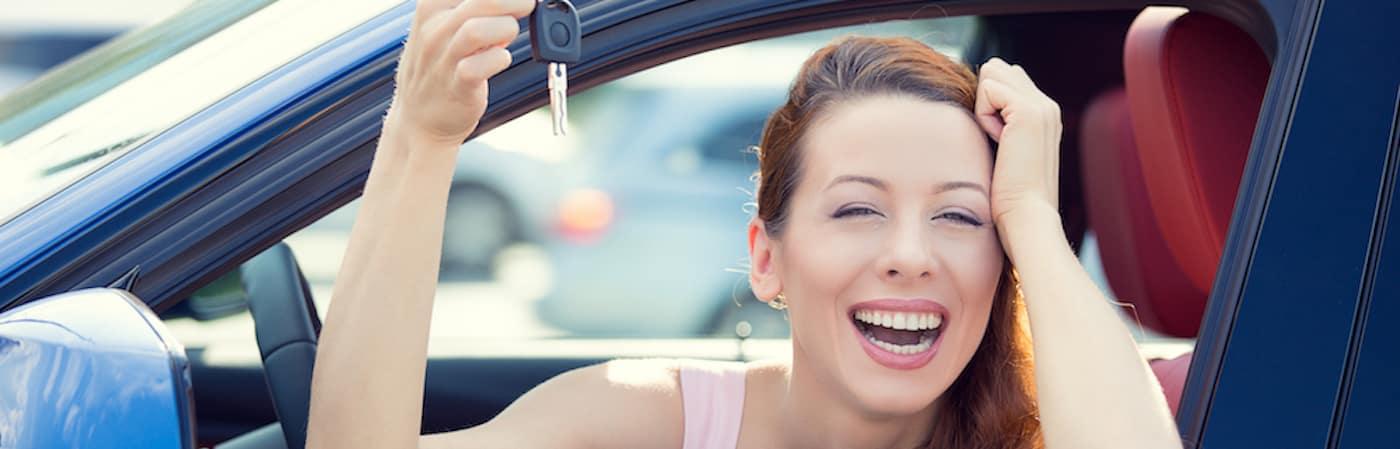 Mujer riendo en el asiento del conductor con las llaves del coche