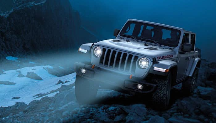Jeep Wrangler with headlights on driving off-road in dark