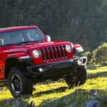 Red Jeep Wrangler Rubicon driving off-road in grassy mountains