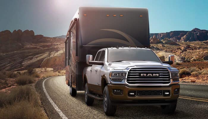 2019 Ram 2500 towing motorhome while driving down desert highway