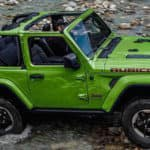 Green 2019 Jeep Wrangler Rubicon driving off-road over rocky terrain