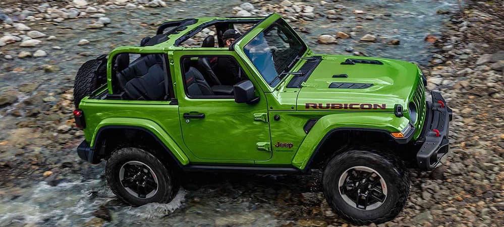Green 2019 Jeep Wrangler Rubicon driving off-road over rocky terrain
