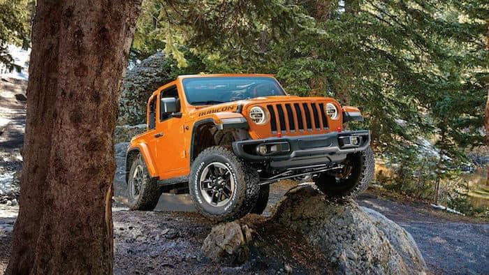 Orange 2019 Jeep Wrangler Rubicon traversing large rocks on forest trail