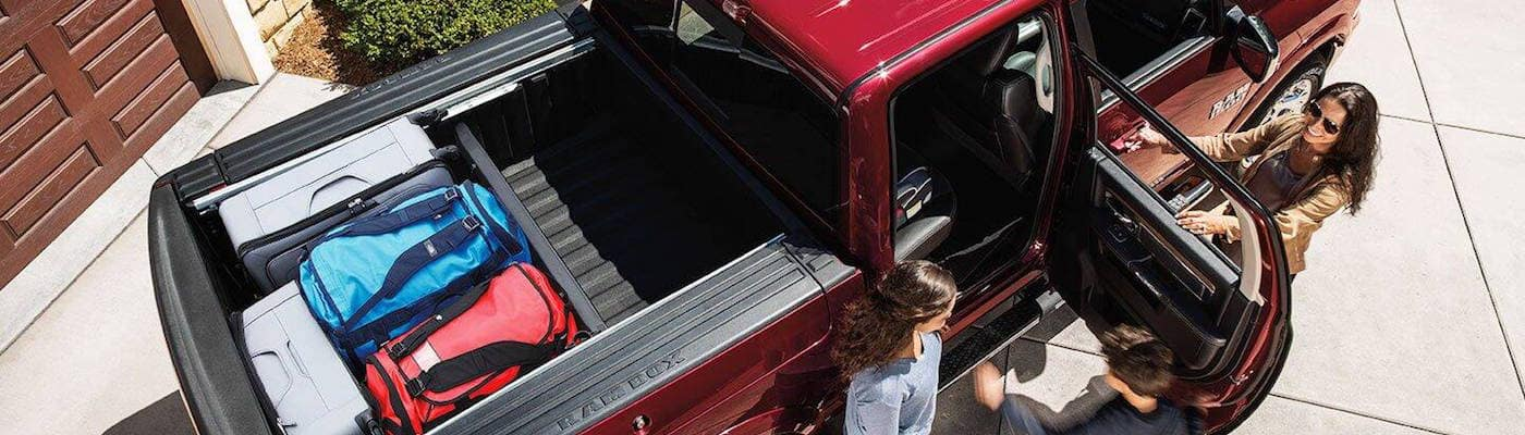 Young boy entering back seat of RAM 1500 Classic with family standing outside vehicle