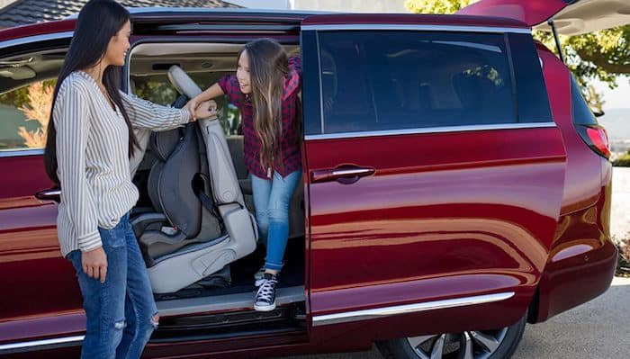 Girl exiting third row of red Chrysler Pacifica with help from her mom